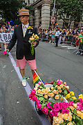 A man wearing pink Bermuda shorts and a straw boater with a wagon of flowers.