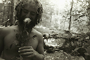 Copyright ©Ê2004 Jeremy Hogan - All Rights Reserved..A hippy smells a rose during regional Rainbow Gathering in the Hoosier National Forest in Southern Indiana...indiana, roses, smelling, black and white, forest, youth, young, 20s, freedom, peace, love, counterculture, hipster,