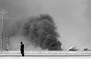 Under the Shadow of War<br /> <br /> Basra, Iraq-- April 5, 2003    A man stands in the outskirts of the city of Basra, Iraq where heavy fighting sitll continues.  The fire in the background is from oil pits that were set on fire by the Iraquis. . photo by  Essdras M Suarez/Globe staff