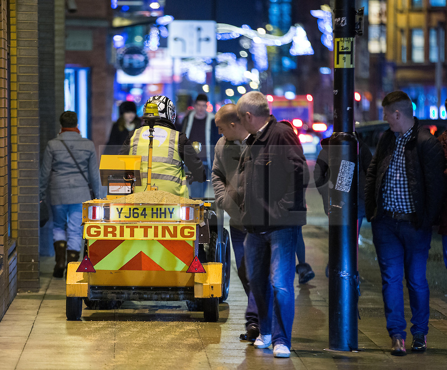 © Licensed to London News Pictures . 05/12/2014 . Manchester , UK . As temperatures fall below freezing and snow is forecast , a modified quad bike with a grit hopper towed behind is driven along pavements in Manchester City Centre , gritting the walkways in its path . The specialised vehicle shares the pavement with commuters heading home at the end of the week and revellers heading for a night out . Photo credit : Joel Goodman/LNP