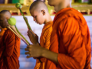 "04 MARCH 2015 - BANGKOK, THAILAND: Buddhist monks participate in a procession around the ""wiharn,"" or prayer hall, at Wat Benchamabophit on Makha Bucha Day. Makha Bucha Day is an important Buddhist holy day and public holiday in Thailand, Cambodia, Laos, and Myanmar. Many people go to temples to perform merit-making activities on Makha Bucha Day. Wat Benchamabophit is one of the most popular Buddhist temples in Bangkok.    PHOTO BY JACK KURTZ"