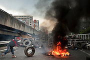 16 MAY 2010 - BANGKOK, THAILAND: An anti government Red Shirt puts more tires on a burning barricade in Bangkok Sunday. Thai troops and anti government protesters clashed on Rama IV Road again Sunday afternoon in a series of running battles. Troops fired into the air and unidentified snipers shot at pedestrians on the sidewalks. At one point Sunday the government said it was going to impose a curfew only to rescind the announcement hours later. The situation in Bangkok continues to deteriorate as protests spread beyond the area of the Red Shirts stage at Ratchaprasong Intersection. Many protests now involve people who have not been active in the Red Shirt protests and live in the vicinity of Khlong Toei slum and Rama IV Road. Red Shirt leaders have called for a cease fire, but the government indicated that it is going to go ahead with operations to isolate the Red Shirt camp and clear the streets.      PHOTO BY JACK KURTZ
