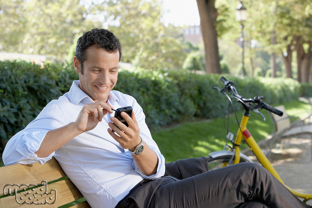 Businessman using palm pilot on park bench
