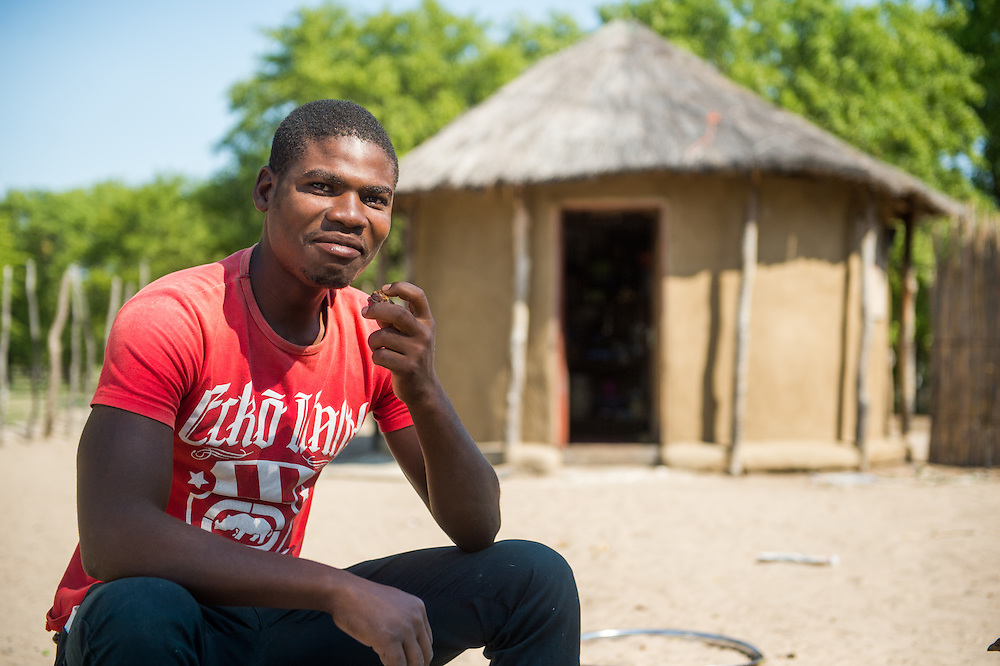 Maun, Botswana, African man sitting in front of thatched roof hut