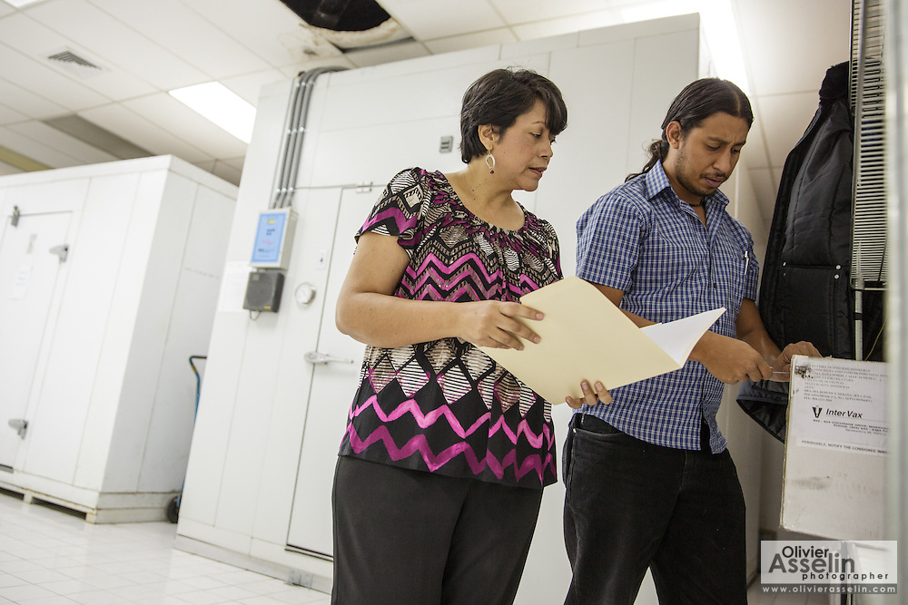 Cold store assistant manager Eddy Godoy discusses with PAI sub-chief Lourdes Mendoza as they check the stocks at the PAI (Programa Ampliado de Inmunizaciones) offices in Tegucigalpa, Honduras, on Wednesday April 24, 2013..