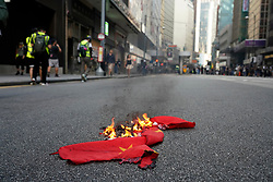 Hong Kong. 1 October 2019. After a peaceful march through Hong Kong Island by an estimated 100,000 pro democracy supporters, violent flared up at Tamar, Admiralty and moved through Wanchai district. Police used teargas and baton rounds and water cannon. Hard core group lit fires, threw bricks and Molotov cocktails at police. Violence continues into evening. Burning Chinese flag in Central.  tram stop. Iain Masterton/Alamy Live News.