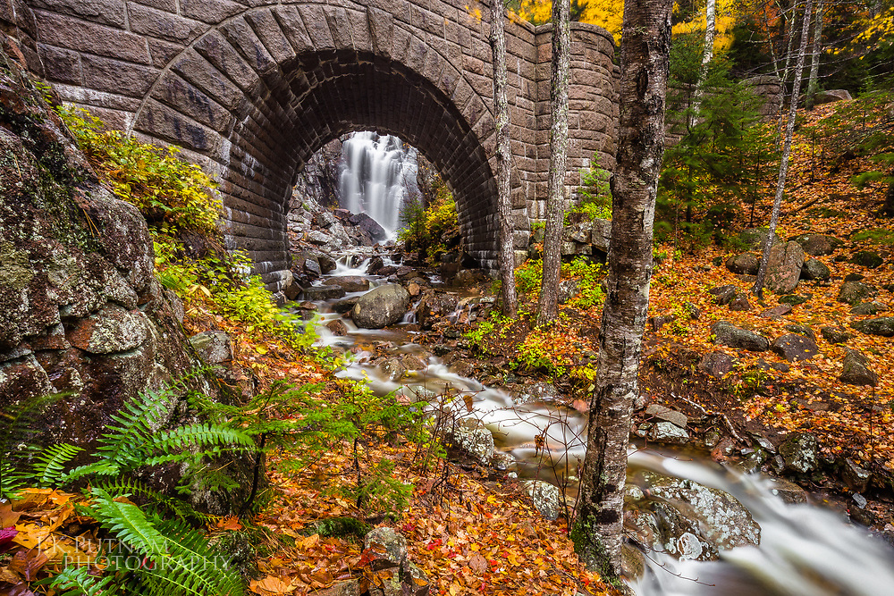 Hadlock Falls seen through the arch of the Waterfall Bridge in fall, Acadia National Park, Mount Desert Island, Maine.
