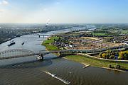 Nederland, Gelderland, Nijmegen, 24-10-2013; rivier de Waal met Waalbrug, gezien vanuit het Oosten, daarachter de spoorbrug met fietspad (De Snelbinder) en tenslotte de nieuwe stadsbrug van Nijmegen De Oversteek. Rechts van de rivier grondwerkzaamheden voor de dijkteruglegging Lent (Ruimte voor de Rivier). De dijken worden landinwaarts verplaats en er wordt een nevengeul gegraven. De huizen op de dijk blijven bestaan en komen te liggen op het Stadseiland Veur-Lent Nijmegen. In de verte de rookpluimen van de energiecentrale Electrabel Nederland.<br /> First bridge the Waal bridge on the river Waal, next the railway bridge with cycle path De Snelbinder (The Luggage strap) and finally the new city bridge of Nijmegen De Oversteek (The Crossing). Right of the river groundwork for the Dike relocation of Lent (project Ruimte voor de Rivier: Room for the River). <br /> luchtfoto (toeslag op standaard tarieven);<br /> aerial photo (additional fee required);<br /> copyright foto/photo Siebe Swart.