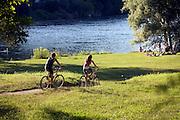 Two cyclists run along the left riverside of Ticino to the public beach at Golasecca, Varese. ..Due ciclisti vanno verso la spiaggia comunale di Golsecca lungo la riva sinistra del fiume Ticino, Varese.