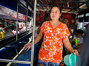 13 APRIL 2018 - BANGKOK, THAILAND:  A woman in the back of songthaew (pickup truck converted to bus) gets hit with water during a water fight on Silom Road on the first day of Songkran in Bangkok. Songkran is the traditional Thai New Year celebration best known for water fights.    PHOTO BY JACK KURTZ