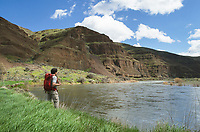 Hiker with red backpack looking out over John Day River, Cottonwood canyon State Park, Oregon