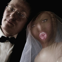 A man in a dinner jacket with a blow up doll bride