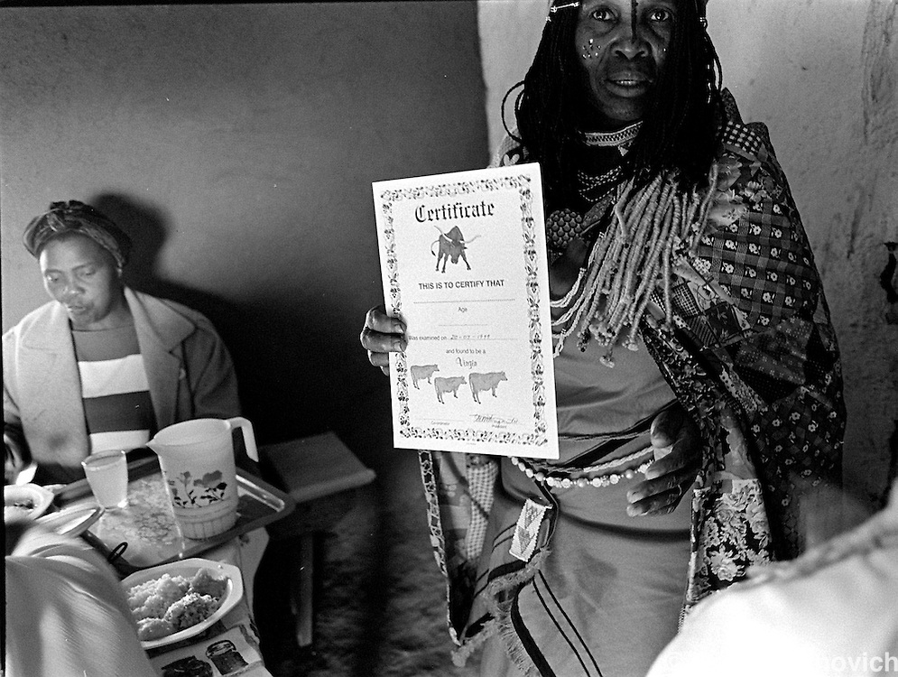 A mother holds up the ceretificate her daughter was awarded, authenticating that she was still a virgin after two years of being exammined by a group of mothers in Magqabasini village, near Flagstaff in the former Transkei July 21, 1999.  This tradition has been revived to combat child abuse and high rates of teenage pregnancies and the spread of HIV. (Greg Marinovich)