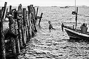 Ein Fischer hangelt sich von seinem Boot an den Steg