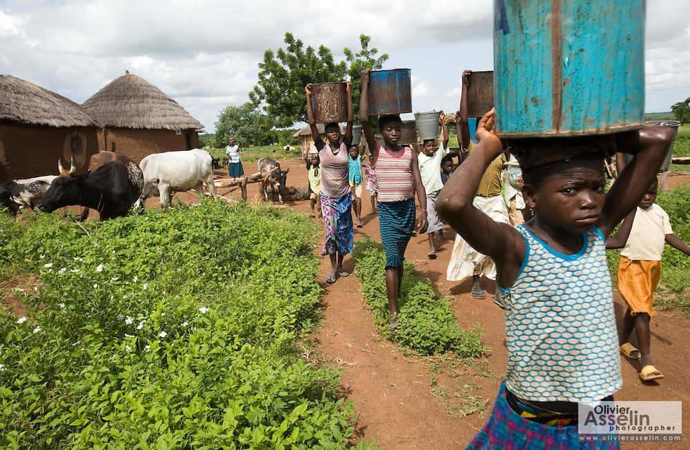 A group of girls carry water buckets on their heads as they walk back home from a borehole situated 15 minutes away from the village of Ying, in the Savelugu-Nanton district, northern Ghana on Monday June 4, 2007.
