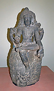 Shiva as Dakshinamurti ('Lord who faces South'), represents Shiva as the supreme teacher. (1200-1300)  Late Chola period.  Granite, Southern India.  Holding a rosary and flame, he expounds the sacred texts and has the uncut hair of an ascetic.