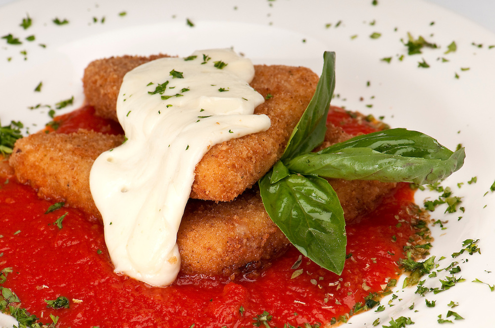 Plate of fried mozzarella with marinara sauce, parsley and melting mozzarella on top.