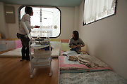 Asawa Pet Pasture elder care for Dogs, Pet of Owners who can not give the  care they feel  their pet deserves.<br /> Saito  Yuki   (rt) consults with her co worker Kana Okazaki while feed ing Pink they are providing the  extra care need to  elderly dogs or dogs with special needs.<br /> for story by Richard Lloyd Parry