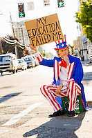 "Uncle Sam sitting on a milk crate on the side of a street holding a sign that says ""my education failed me""...Model Release: 20080813_MR_A"