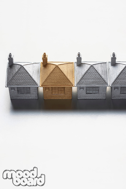 One gold model house in row of grey ones