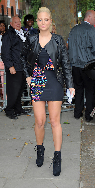 Tulisa Contostavlos wearing a black leather jacket over a short black dress with rainbow pattern and lace up boots, left Live Lounge BBC Radio 1 Studios in Maida Vale to waiting fans. London. UK 28/08/2012<br />