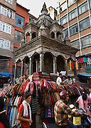 Men sell colorful scarves at an old temple surrounded by modern buildings in Kathmandu, the largest city in Nepal (700,000 people), which is sometimes called by its Malla Dynasty name of Kantipur. The original inhabitants of Kathmandu Valley are Newars, who speak the language Nepal Bhasa. However, Nepali is the lingua franca of the valley and is the most widely spoken language. The city stands at an elevation of 6235 feet / 2230 meters.