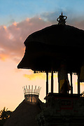 "Sunset silhouette of the crown of a Fivelements ""mandala"" tower, alongside a traditional Balinese temple."