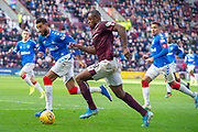 Uche Ikpeazu (#19) of Heart of Midlothian FC bursts into the Rangers box, as he is watched by Connor Goldson (#6) and James Tavernier (#2) of Rangers FC during the Ladbrokes Scottish Premiership match between Heart of Midlothian and Rangers FC at Tynecastle Park, Edinburgh, Scotland on 20 October 2019.