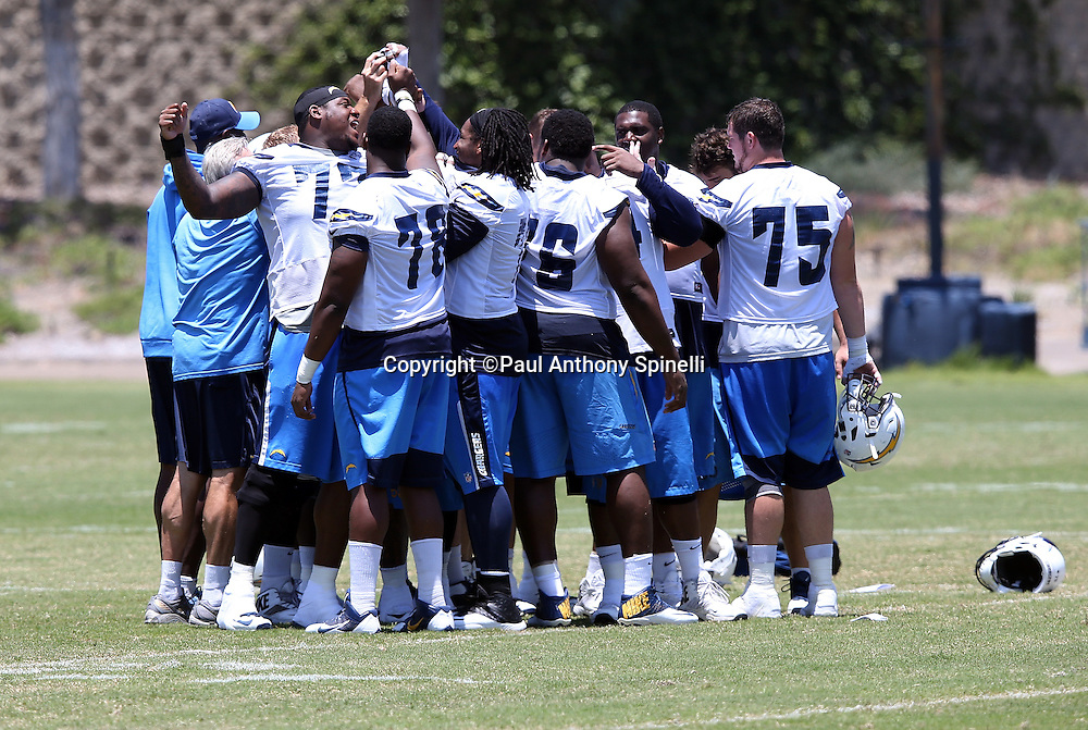San Diego Chargers players huddle up in a group and join hands after the San Diego Chargers Spring 2015 NFL minicamp practice on Wednesday, June 17, 2015 in San Diego. (©Paul Anthony Spinelli)