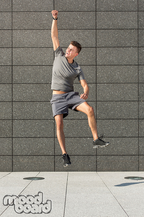 Full length of excited jogger jumping against tiled wall