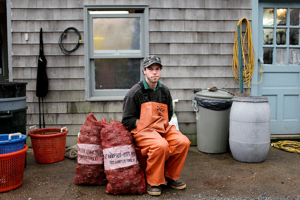 Zach is a first generation East Hampton local.  He lives on a compound of other commercial fishermen called Poseyville.  The yards are set up to accomodate multiple commercial vehicles, boats, nets and traps.  The building behind him was designed so multple people could stand at a bench and shuck scallops simultaneously.  They sell fish wholesale but also directly from this building.