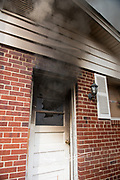 Smoke billows out the window of a door in a burning house.