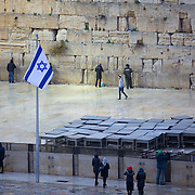 An Israeli flag waves as snow and rain fall at The Western Wall on January 7, 2015 in Jerusalem, Israel. (Photo by Elan Kawesch)