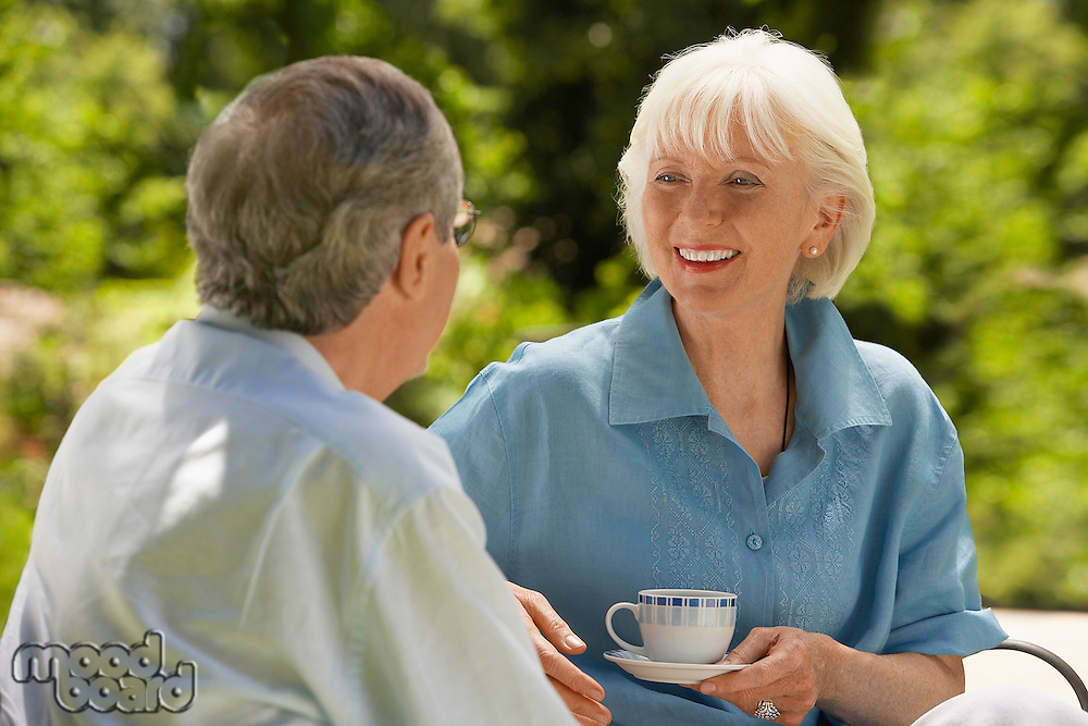 Middle-aged Couple Talking on sofa in back yard head and shoulders