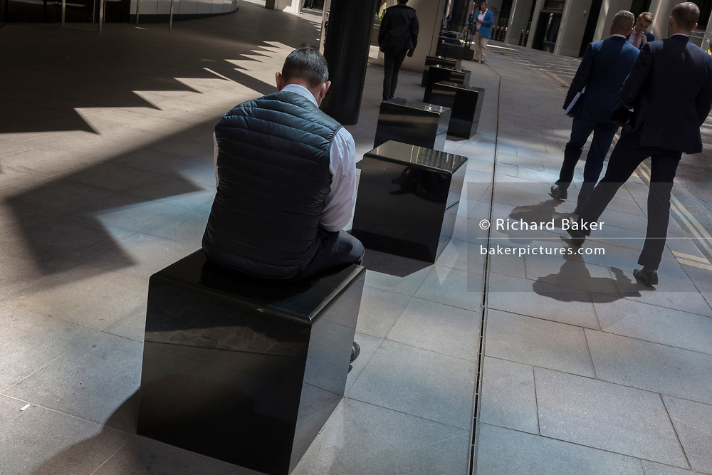 A financial services worker sits on a sunlit corner of Fenchurch Avenue in the City of London, the capital's financial district aka the Square Mile, on 17th May 2018, in London, UK.