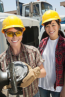 Portrait of female industrial worker buffing a truck engine cylinder with coworker standing besides her