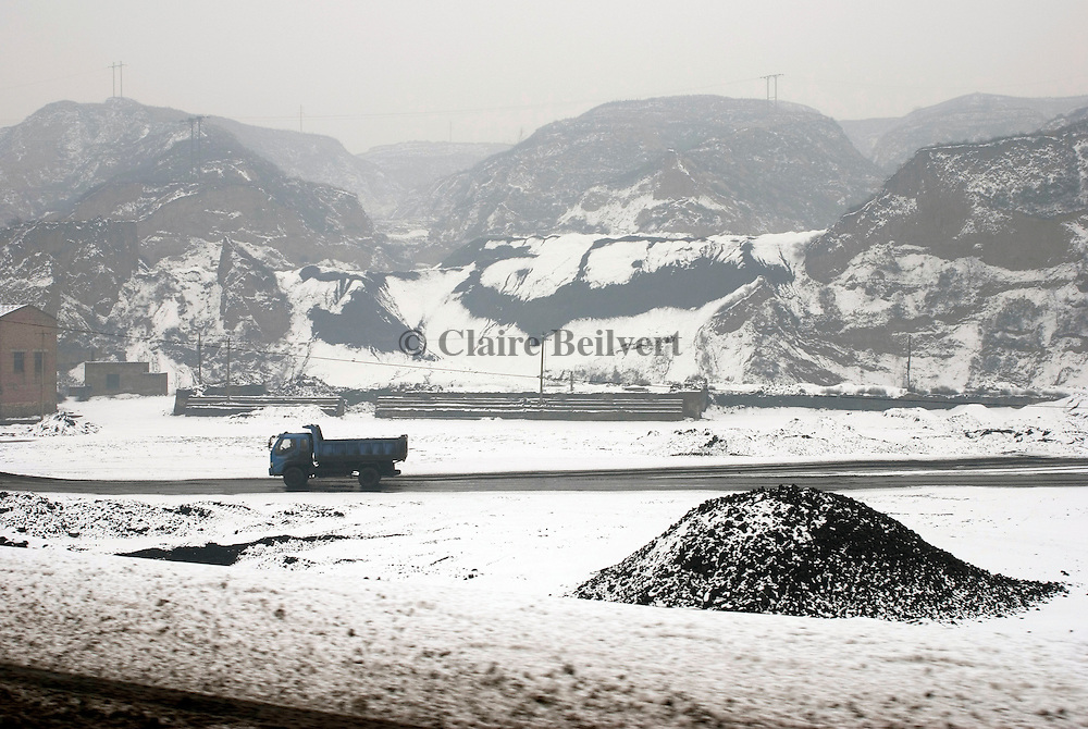Coal truck on a road. Days and nights hundreds of trucks are conveying coal. This Province is China's largest coal supplier with 500 millions of tonnes each year. It is also the most polluted of the country. Roads and trucks are covered with coal.