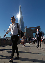 © Licensed to London News Pictures. 19/07/2016. LONDON, UK.  Commuters walk to work over London Bridge as the sun reflects on the London Shard during hot weather in London this morning. Today is forecast to be the hottest day of the year so far.  Photo credit: Vickie Flores/LNP