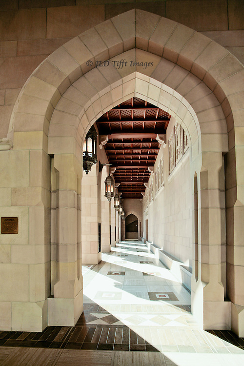Muscat, Grand Mosque of Sultan Qaboos, view down an arcade that borders the courtyard of the mosque.  Sunlight streaming between the pillars, casting parallel shadows.  Carved woodehn [teak] ceiling, pointed arch at entrance.