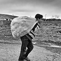 A Syrian refugee carries a bag outside of his camp in Reyhanli, Turkey, Friday, March 16, 2012. The number of Syrian refugees in Turkey is now about 17,000. March 2012.