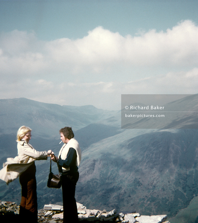 A young couple stand with the backdrop of Welsh mountains and hills in the background in the 1970s. Helping her husband to light his cigarette in a breeze, the woman's coat is blowing in the wind, so high up in the mountains have they stopped during a daytrip to the north Welsh hills. Rolling misty mountains are in the distance as bad weather appears to be approaching. It was taken on a film camera by the man's father, an amateur photographer in 1973. The picture shows us a memory of nostalgia in an era from the last century.