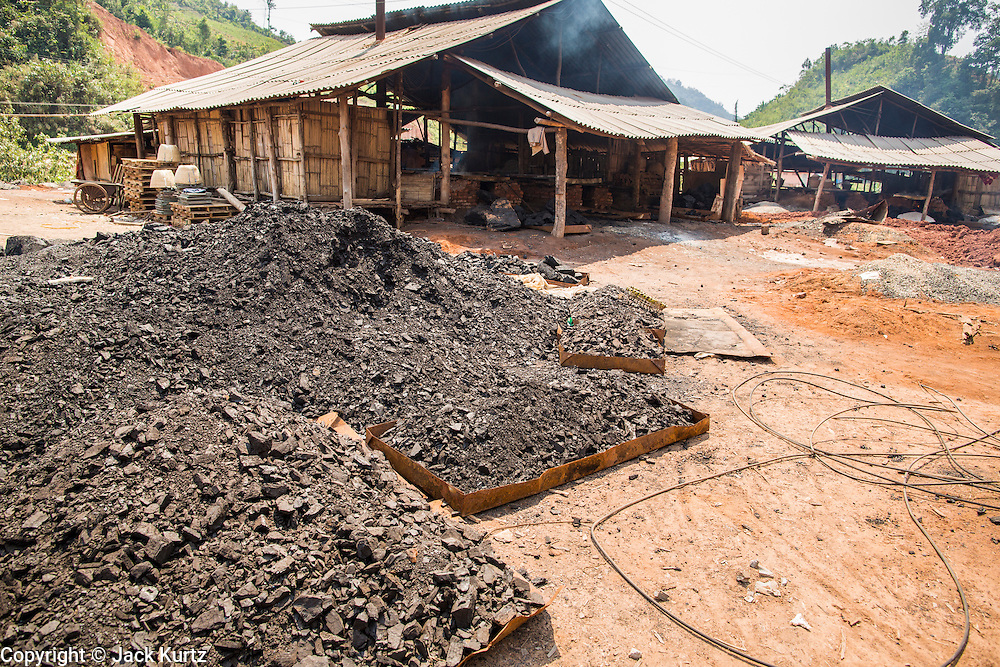 13 MARCH 2013 - BOTEN, LUANG NAMTHA, LAOS: Charcoal stacked up in front of salt workshops in Boten, Laos. The fires that boil the brine are charcoal fueled. Salt in Boten is made by boiling briny water and collecting the salt that is left behind. The salt wells in Boten, Laos, just south of the Chinese border, have brought a measure of fame to the area for centuries. French forces asserted French dominance over the region in 1894 to control the salt trade. Some of the salt works face an uncertain future because of economic development from China. The area is being developed into a huge parking lot to accommodate truck and tourist traffic into and out of China. PHOTO BY JACK KURTZ