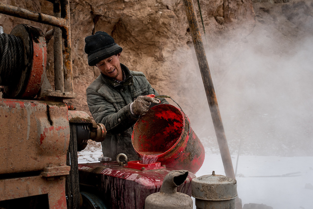 A worker pours a bucket of river water into the cooling tank of his machinery. The team is taking earth samples from the river bed in preparation for the construction of a new bridge over the Mekong in Zado, Tibet (Qinghai, China).