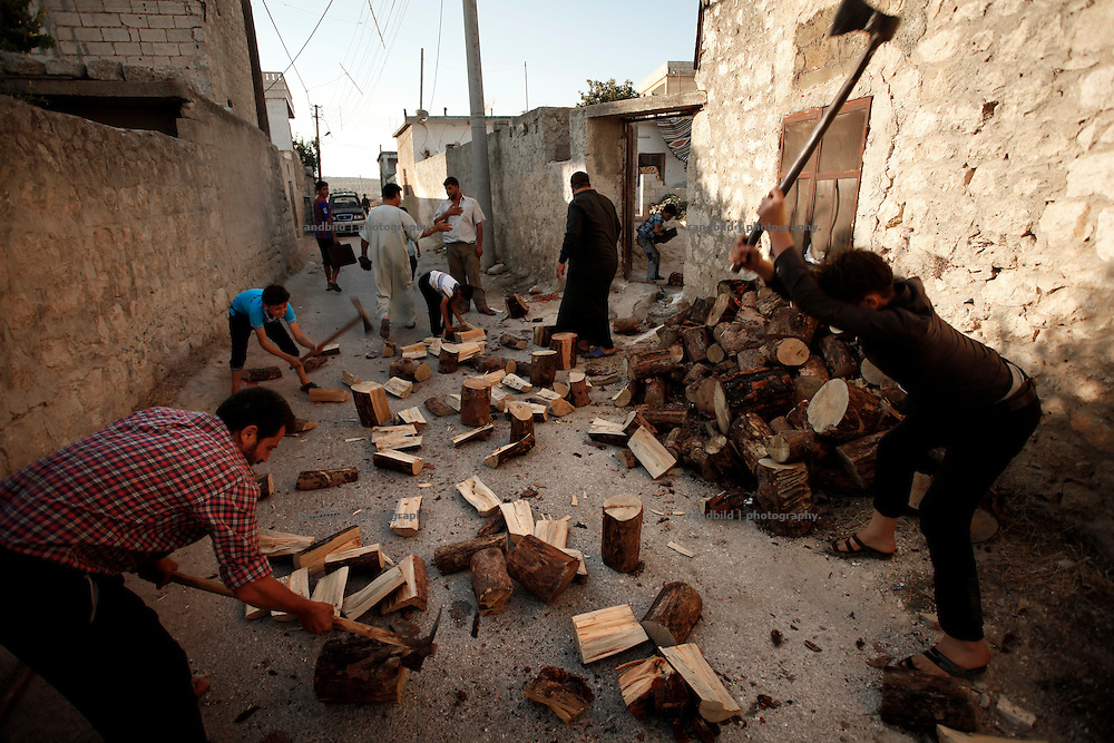 People chop fire wood in their nighbourhood in the village Koreen. Especially winter is challenging for syrians in this almost four years lasting civil war.<br /> _ _ _ <br /> Idlib Interim - Challenging life without central government in the village of Koreen (Idlib Province, Syria)<br /> Koreen joint the syrian uprisung to ouster president Bashar al-Assad at a very early stage in 2011. It has been scene of Army attacks and heavy shelling since 2012. In the course of the fightings the village of a few thousend inhabitants was almost abandoned as barrel bomb campaings commited by the regime pounded Koreen. But since regime forces retreated to few bases remaining in Idlib province people returned home to establish a new and almost unregulated economic, social and community life. The regimes power has no affect and can&acute;t reach them anymore. On the other hand a new government isn&acute;t established yet and not in sight at all. Koreen is free to make its way.