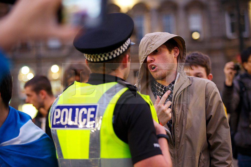 © Licensed to London News Pictures. 19/09/2014. Glasgow, UK. Disappointed 'Yes' voters and campaigners debating with police officers as they react to Scotland's decision to stay in the union at George Square in Glasgow on Friday, 19 September 2014, after the Scottish independence referendum. Photo credit : Tolga Akmen/LNP