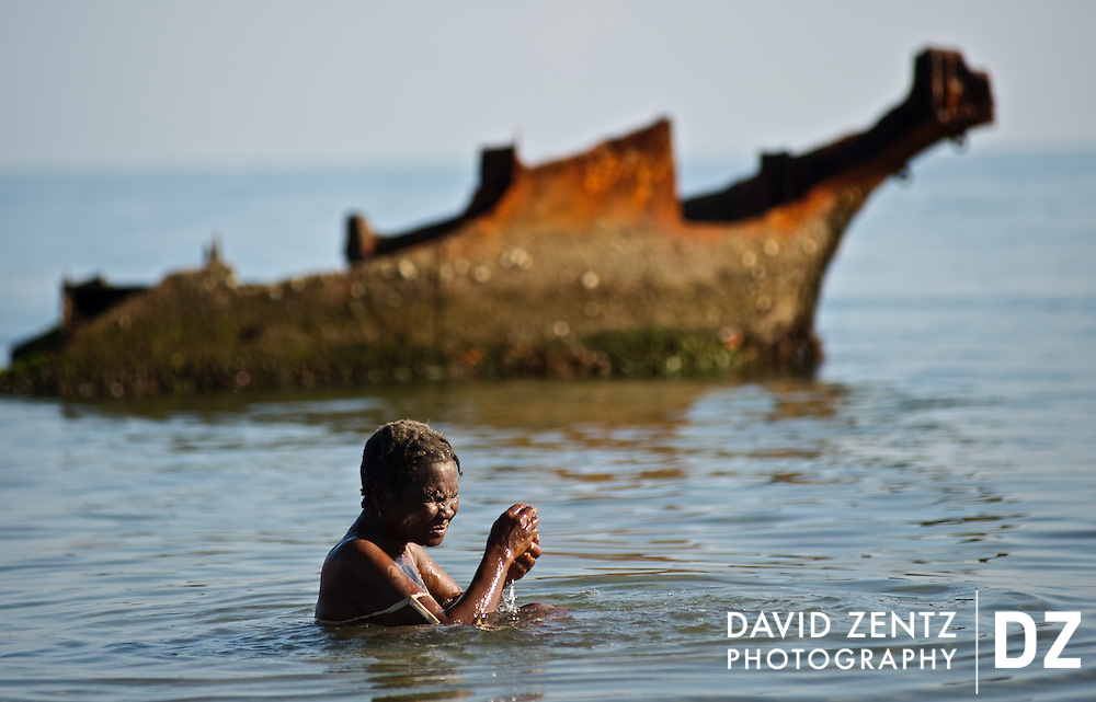 A pilgrim watches bathes in the sea during in front of the rusted wreckage of a ship during a sunrise voodou ritual at Bord de Mer de Limonade, on the north coast of Haiti on July 25, 2008. After renewing their faith in the mud pit at Plaine du Nord on the days prior, pilgrims migrate to the nearby water, their faith renewed. The site is also where Christopher Columbus' Santa Maria sank in 1492.