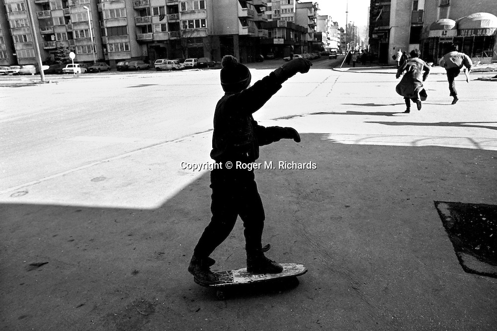 Aldin Jogic balances on his skateboard and watches as two adults race across an intersection under Serb sniper fire in Sarajevo, Bosnia-Herzegovina, February 1993. PHOTO BY ROGER RICHARDS