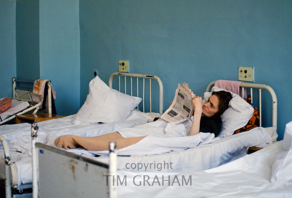 Patient reading Russian newspaper in ward of hospital in St Petersburg, Russia