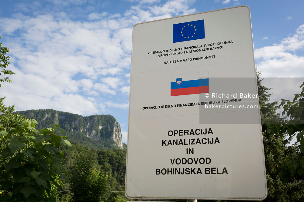 A signpost for European Union funding of a sewage and water supply project in a rural Slovenian village, on 18th June 2018, in Bohinjska Bela, Bled, Slovenia.