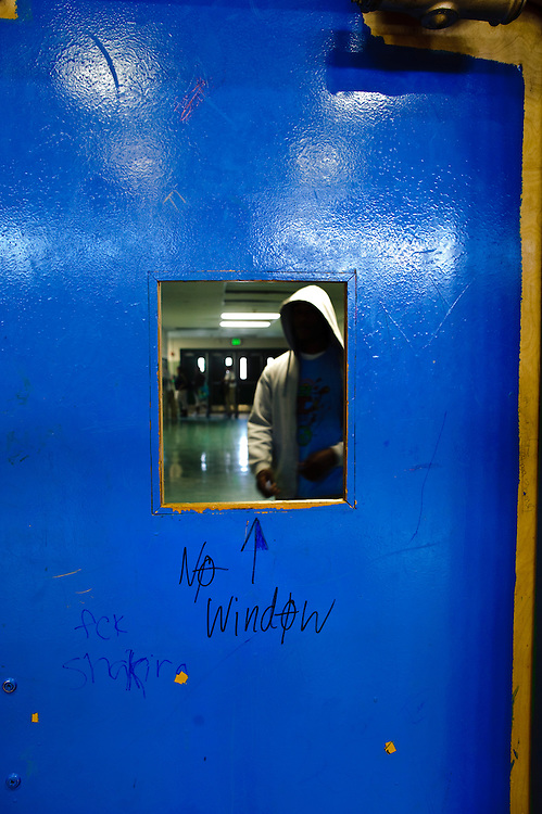(photo by Matt Roth).Friday, May 14, 2010..A student approaches one of the Baltimore Freedom Academy gym doors which is missing a window pane. The building housing the Baltimore Freedom Academy, a grade 6-12 Baltimore public charter school focusing in social justice, was built in 1960. Fifty years later, the school is in disrepair. Old pipes make water from the fountains undrinkable. Asbestos makes repairing/replacing the pipes a hazard. The school has no air conditioning which makes the year-round school unbearable in the summer. The most derelict area is the boys locker room, where students are not allowed.